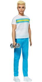 Poupée Ken 60ème anniversaire dans une tenue rétro composée d'un t-shirt, d'un pantalon de style sportif, de baskets et d'un haltère